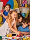 Kleine Studentenmädchen-Fingermalerei in der Kunstschulklasse Stockfotografie