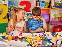Kleine Studentenmädchenmalerei in der Kunstschulklasse Stockfotografie