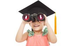 Kleine Studentin, die durch Ferngläser schaut Lizenzfreies Stockfoto