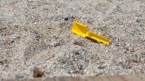 Kleine stuk speelgoed schop op het zand stock foto