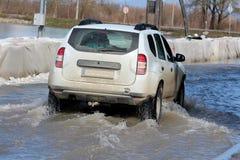 Kleine SUV-auto die door overstroomde straat overgaan Stock Foto