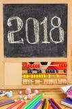 Kleine Tafel im hölzernen Abakusrahmen und in Hand geschriebenem Gruß des neuen Jahres 2018 auf ihm Zerstreutes Briefpapier, bunt Stockfotografie