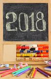 Kleine Tafel im hölzernen Abakusrahmen und in Hand geschriebenem Gruß des neuen Jahres 2018 auf ihm Zerstreutes Briefpapier, bunt Lizenzfreies Stockbild