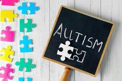 Kleine Tafel mit Wort AUTISMUS und Puzzlespiele Stockfotografie