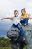 Kleine tapfere Kinder auf einem Dinosaurier in einem Park Lizenzfreies Stockbild