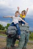 Kleine tapfere Kinder auf einem Dinosaurier in einem Park Lizenzfreie Stockfotos