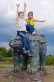 Kleine tapfere Kinder auf einem Dinosaurier in einem Park Lizenzfreie Stockfotografie