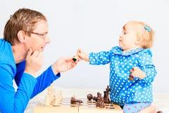 Kleine Tochter, die Schach mit Vater spielt Lizenzfreies Stockfoto