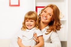 Kleine Tochter mit Mutter zu Hause Stockbilder