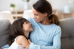 Kleine Tochter und junge Mutterumarmung, die auf Couch sich entspannt lizenzfreies stockbild