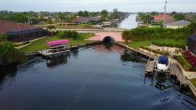 Kleine toeristenboot die langzaam onder brug in het blauwe water van de kanaalrivier in tropisch landschap in verbazend lucht4k s stock video