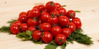 Kleine Tomaten und frische Kräuter auf hölzernem Hintergrund Stockbilder
