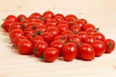 Kleine Tomaten und frische Kräuter auf hölzernem Hintergrund Stockbild