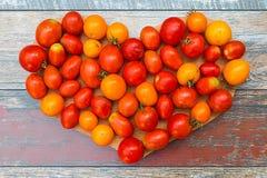 Kleine Tomaten vereinbart in der Herzform stockfotos