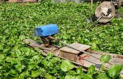 Kleine traditionele houten die boot door waterhyacint wordt omringd in plattelandsvijver in Thailand royalty-vrije stock afbeeldingen