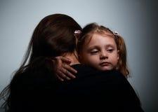 Kleine traurige Tochter, die ihre Mutter mit Liebe auf Dunkelheit umarmt Lizenzfreie Stockfotografie