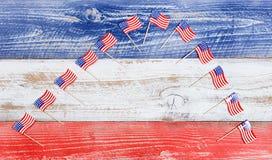 Kleine USA-Flaggen in der Bogenbildung auf rustikalen Brettern mit Staatsangehörigem Lizenzfreies Stockfoto