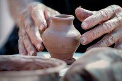 Kleine vaas en handen van een pottenbakker Stock Afbeeldingen