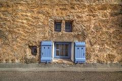 Kleine vensters in een rustieke muur stock foto