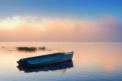 Kleine vissersboot die dichtbij mist op rivier wordt verankerd Stock Foto