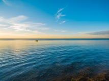 Kleine vissersboot die op ondiep water bij schemer drijven royalty-vrije stock afbeelding