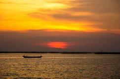 Kleine vissersboot met zonsonderganglicht stock afbeelding