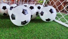 Kleine voetbal op grasachtergrond stock foto