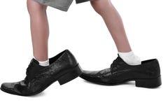 Kleine voeten in grote schoenen Stock Fotografie