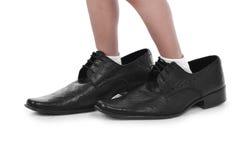 Kleine voeten in grote zwarte schoenen Stock Foto's