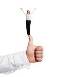 Kleine vrouw die zich op grote duim bevindt Stock Foto