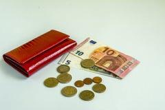 Kleine vrouwen rode portefeuille Bankbiljetten van 5 en 10 euro Sommige muntstukken Achtergrond voor een uitnodigingskaart of een Stock Fotografie