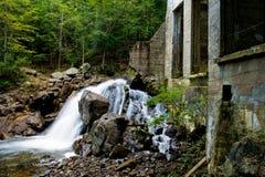 Kleine Wasserfälle nahe einem verlassenen Gebäude Stockbild