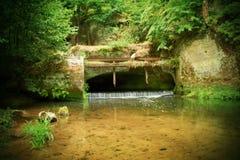 Kleine waterkering op rivierstromen uit van hol Koud water van kleine rivierstroom over kleine steenachtige waterkering Steenacht Stock Foto's