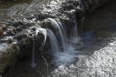 Kleine waterval in bosstroom stock afbeelding