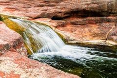 Kleine waterval op rode rots Royalty-vrije Stock Afbeelding