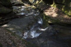 Kleine waterval over het bed van de rotskreek royalty-vrije stock foto's