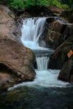 Kleine watervallen die door rotsen in aard vloeien stock foto