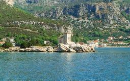 Kleine weiße Kirche auf der Insel, dem Mittelmeer und dem Hochgebirge im Hintergrund Lizenzfreie Stockbilder