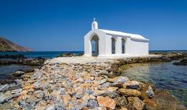 Kleine weiße Kirche im Meer nahe Georgioupolis-Stadt auf Kreta-Insel Lizenzfreie Stockfotos