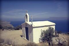 Kleine weiße Kirche und griechische Flagge Stockfotografie