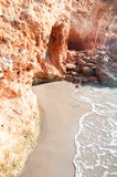 Kleine Welle trifft roten Felsen Lizenzfreies Stockfoto