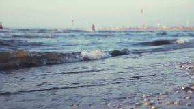 Kleine Wellen des Meeres, auf dem Ufer, an einem vollen Tag mit einer Stadt im Hintergrund stock video