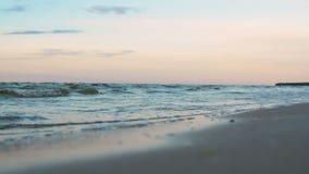 Kleine Wellen, die langsam auf Strand im blauen Abendlicht des Dämmerungssonnenuntergangs rollen stock video