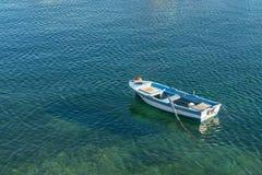 Kleine witte blauwe die boot met peddels op de kust worden verankerd stock afbeelding