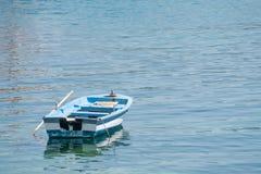 Kleine witte blauwe die boot met peddels op de kust worden verankerd royalty-vrije stock afbeelding
