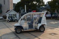 Kleine witte elektrische politiewagen, patrouille met fouten in het park stock foto's