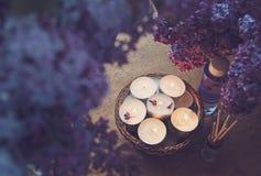 Kleine witte kaarsen in een mand, een massageolie en een essentie Stock Foto