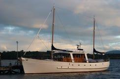 Kleine witte varende die boot bij dok bij stof wordt vastgelegd royalty-vrije stock afbeeldingen