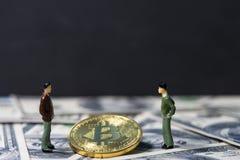 Kleine Zahlen die stehenden Geschäftsmänner der Miniaturleute und sprechen über Geschäft zwischen goldenem bitcoin auf hundert Do Stockbilder