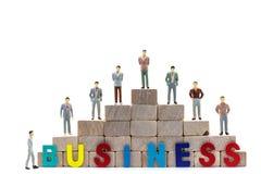 Kleine Zahlen Geschäftsmänner stehen und betrachten Holzklotztreppenhaus Lizenzfreie Stockfotografie